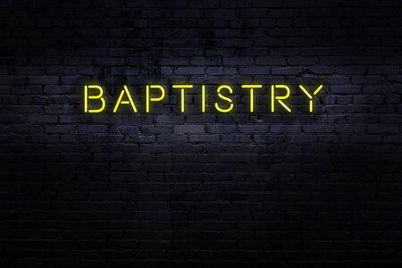 Neon sign on brick wall at night. Inscription baptistry