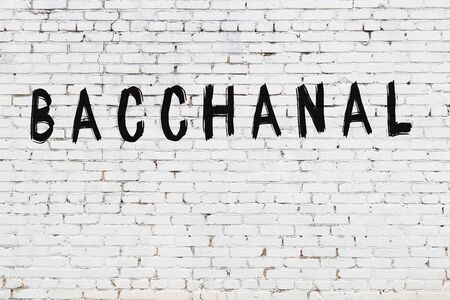 Word bacchanal written with black paint on white brick wall.