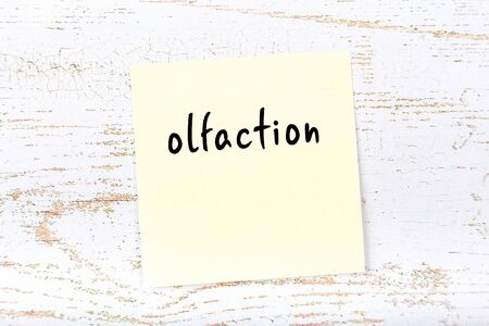 Concept of reminder about olfaction. Yellow sticky sheet of paper on wooden wall with inscription