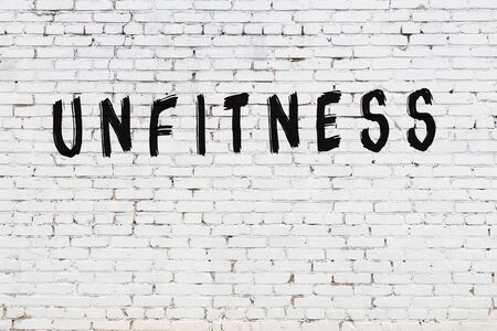 Word unfitness written with black paint on white brick wall. Banco de Imagens