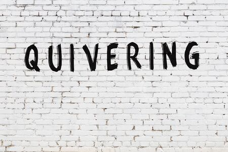 Word quivering written with black paint on white brick wall.