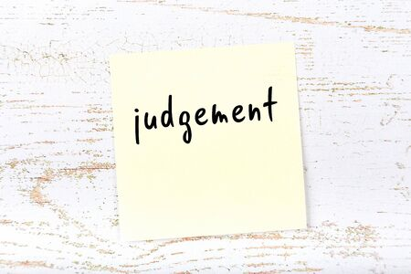 Concept of reminder about judgement. Yellow sticky sheet of paper on wooden wall with inscription Imagens