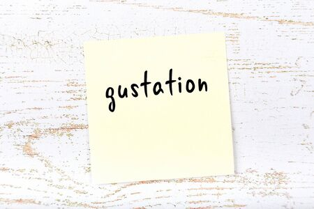 Concept of reminder about gustation. Yellow sticky sheet of paper on wooden wall with inscription