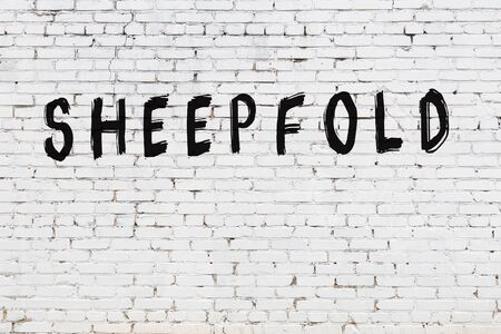 White brick wall with inscription sheepfold handwritten with black paint