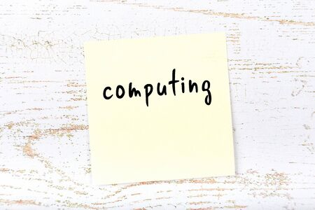 Yellow sticky note on wooden wall with handwritten inscription computing