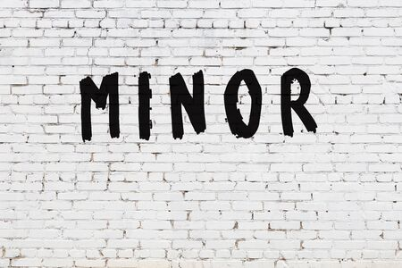Word minor written with black paint on white brick wall.