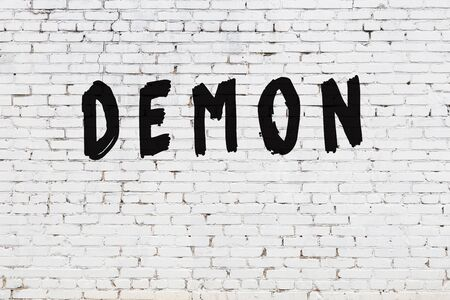 White brick wall with inscription demon handwritten with black paint