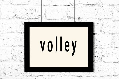 Black wooden frame with inscription volley hanging on white brick wall Stok Fotoğraf