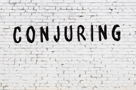 Word conjuring written with black paint on white brick wall. Standard-Bild