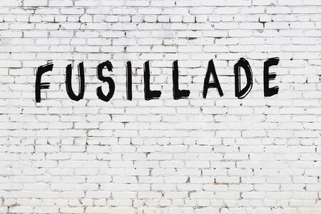 White brick wall with inscription fusillade handwritten with black paint