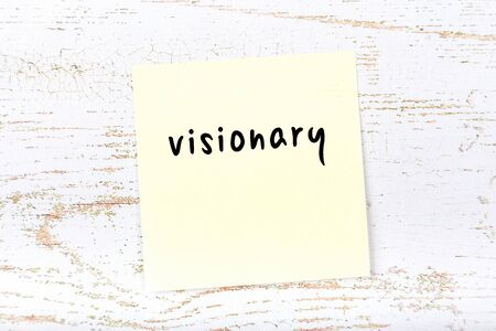 Concept of reminder about visionary. Yellow sticky sheet of paper on wooden wall with inscription