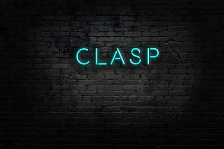Neon sign with inscription clasp against brick wall. Night view