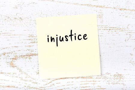 Concept of reminder about injustice. Yellow sticky sheet of paper on wooden wall with inscription Foto de archivo