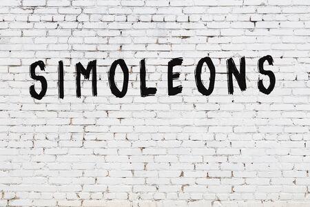 Word simoleons written with black paint on white brick wall.