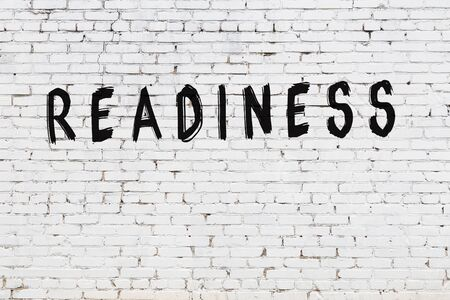 Word readiness written with black paint on white brick wall. Stock Photo