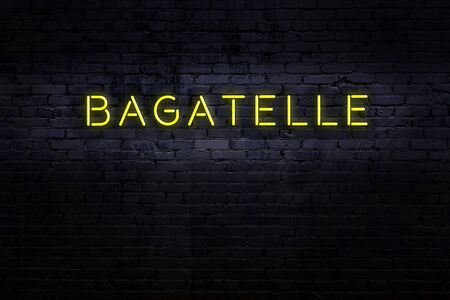 Neon sign on brick wall at night. Inscription bagatelle