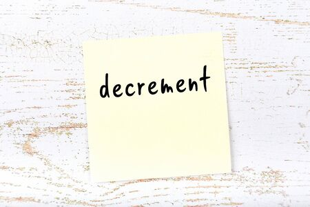 Concept of reminder about decrement. Yellow sticky sheet of paper on wooden wall with inscription 版權商用圖片