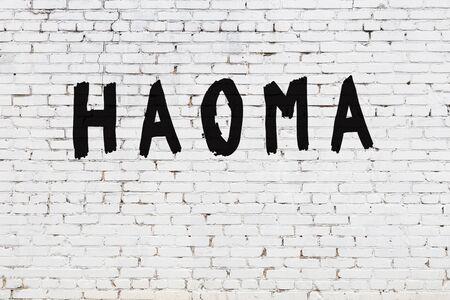 Word haoma written with black paint on white brick wall. Zdjęcie Seryjne