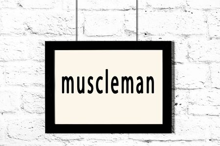 Black wooden frame with inscription muscleman hanging on white brick wall