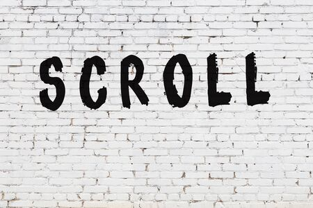 Word scroll written with black paint on white brick wall.