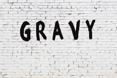 Word gravy written with black paint on white brick wall.