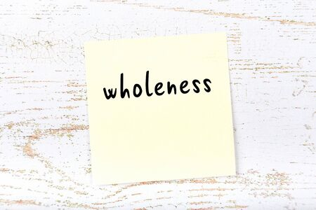 Concept of reminder about wholeness. Yellow sticky sheet of paper on wooden wall with inscription