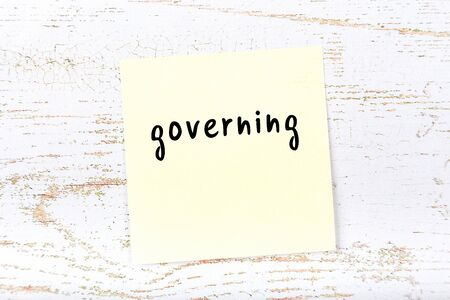 Concept of reminder about governing. Yellow sticky sheet of paper on wooden wall with inscription