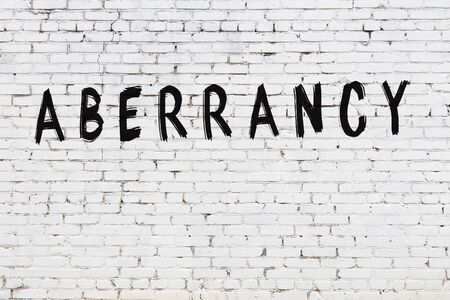 White brick wall with inscription aberrancy handwritten with black paint