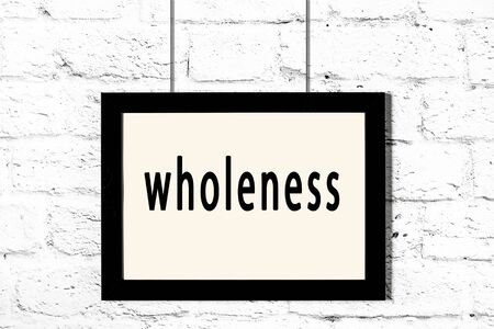 Black wooden frame with inscription wholeness hanging on white brick wall 스톡 콘텐츠