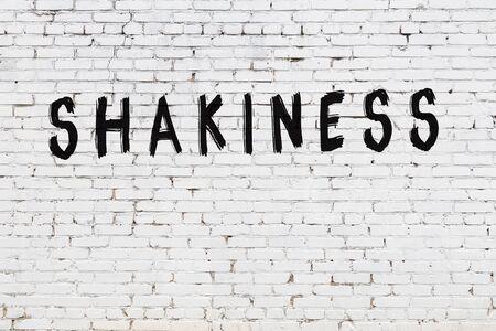 White brick wall with inscription shakiness handwritten with black paint 版權商用圖片