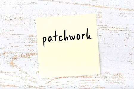 Concept of reminder about patchwork. Yellow sticky sheet of paper on wooden wall with inscription Reklamní fotografie