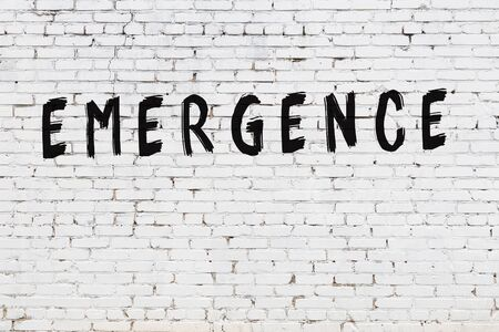Word emergence written with black paint on white brick wall. Foto de archivo
