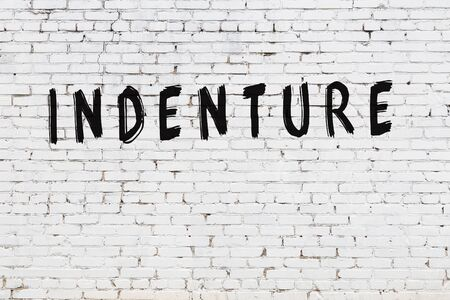 White brick wall with inscription indenture handwritten with black paint