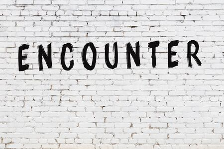 Word encounter written with black paint on white brick wall. 写真素材