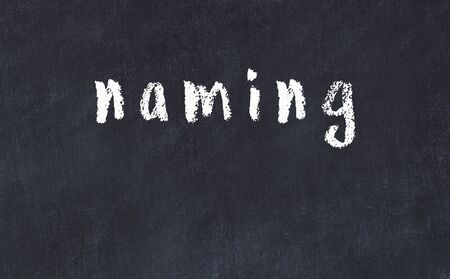 Chalk handwritten inscription naming on black desk