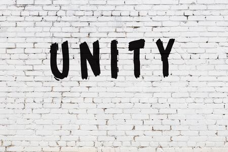 Word unity written with black paint on white brick wall.