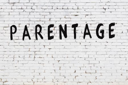 Word parentage written with black paint on white brick wall. Imagens
