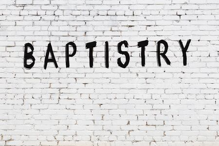 White brick wall with inscription baptistry handwritten with black paint