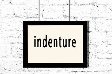 Black wooden frame with inscription indenture hanging on white brick wall