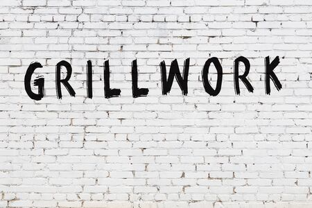 Word grillwork written with black paint on white brick wall. 版權商用圖片