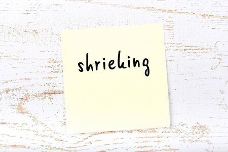 Concept of reminder about shrieking. Yellow sticky sheet of paper on wooden wall with inscription