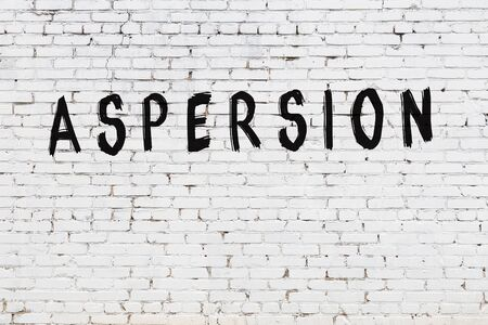 White brick wall with inscription aspersion handwritten with black paint Stok Fotoğraf