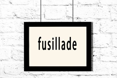 Black wooden frame with inscription fusillade hanging on white brick wall Stok Fotoğraf
