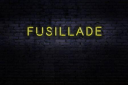 Neon sign on brick wall at night. Inscription fusillade
