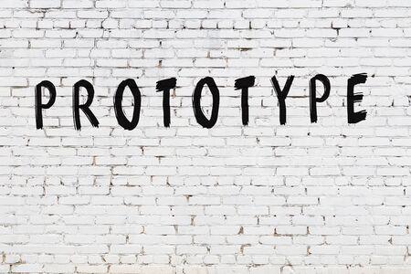 Word prototype written with black paint on white brick wall. Stock Photo