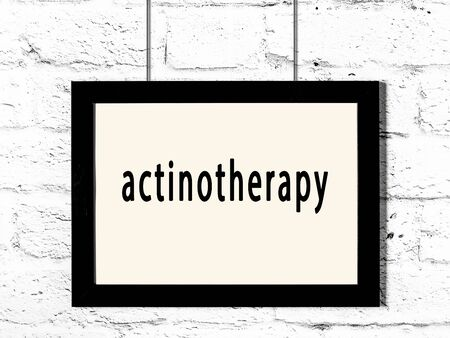 Black wooden frame with inscription actinotherapy hanging on white brick wall