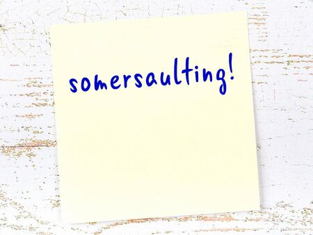 Yellow sticky note on wooden wall with handwritten inscription somersaulting