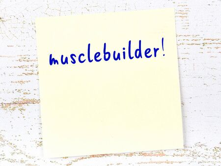 Yellow sticky note on wooden wall with handwritten inscription musclebuilder Standard-Bild