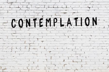 White brick wall with inscription contemplation handwritten with black paint