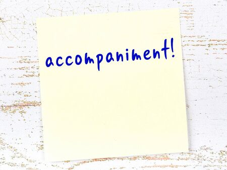 Concept of reminder about accompaniment. Yellow sticky sheet of paper on wooden wall with inscription